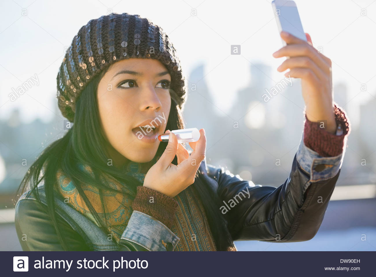 Woman using smart phone to apply lipstick outdoors - Stock Image