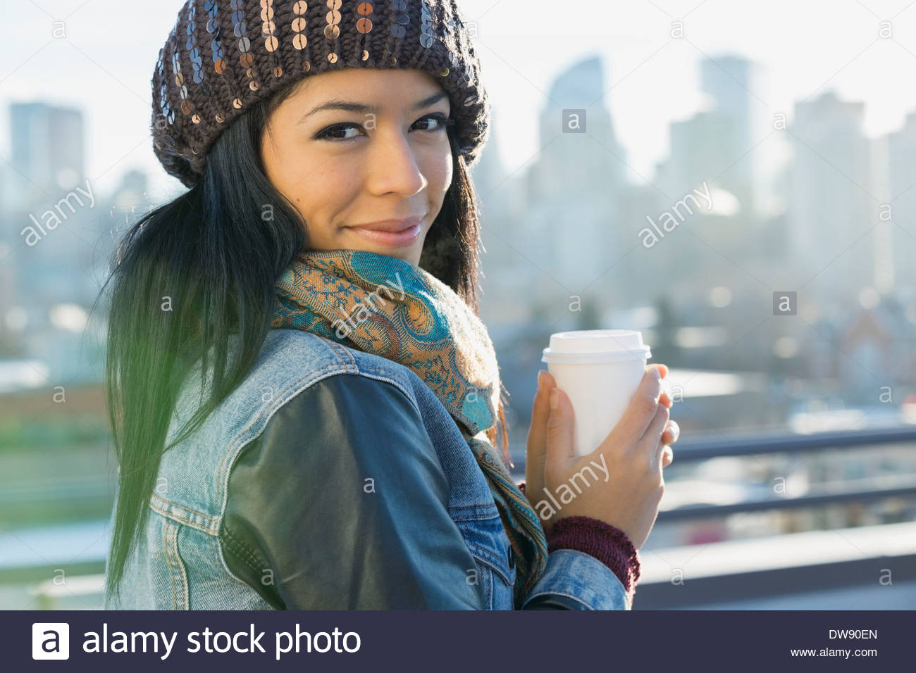 Portrait of woman holding disposable coffee cup - Stock Image