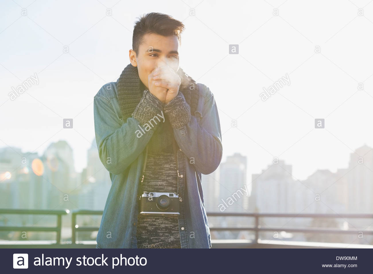 Man standing outdoors warming hands in winter - Stock Image