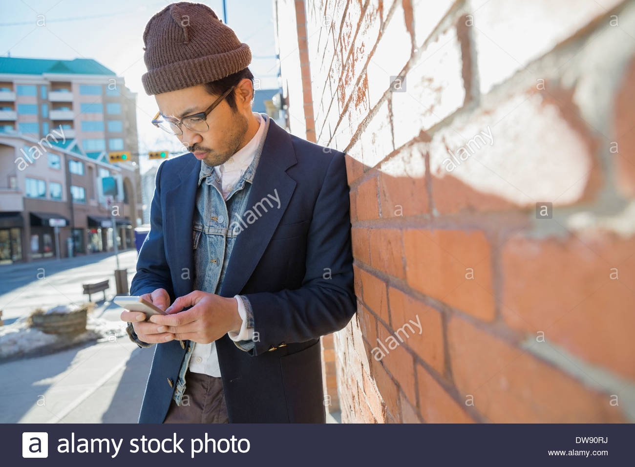 Man text messaging on smart phone against brick wall Stock Photo