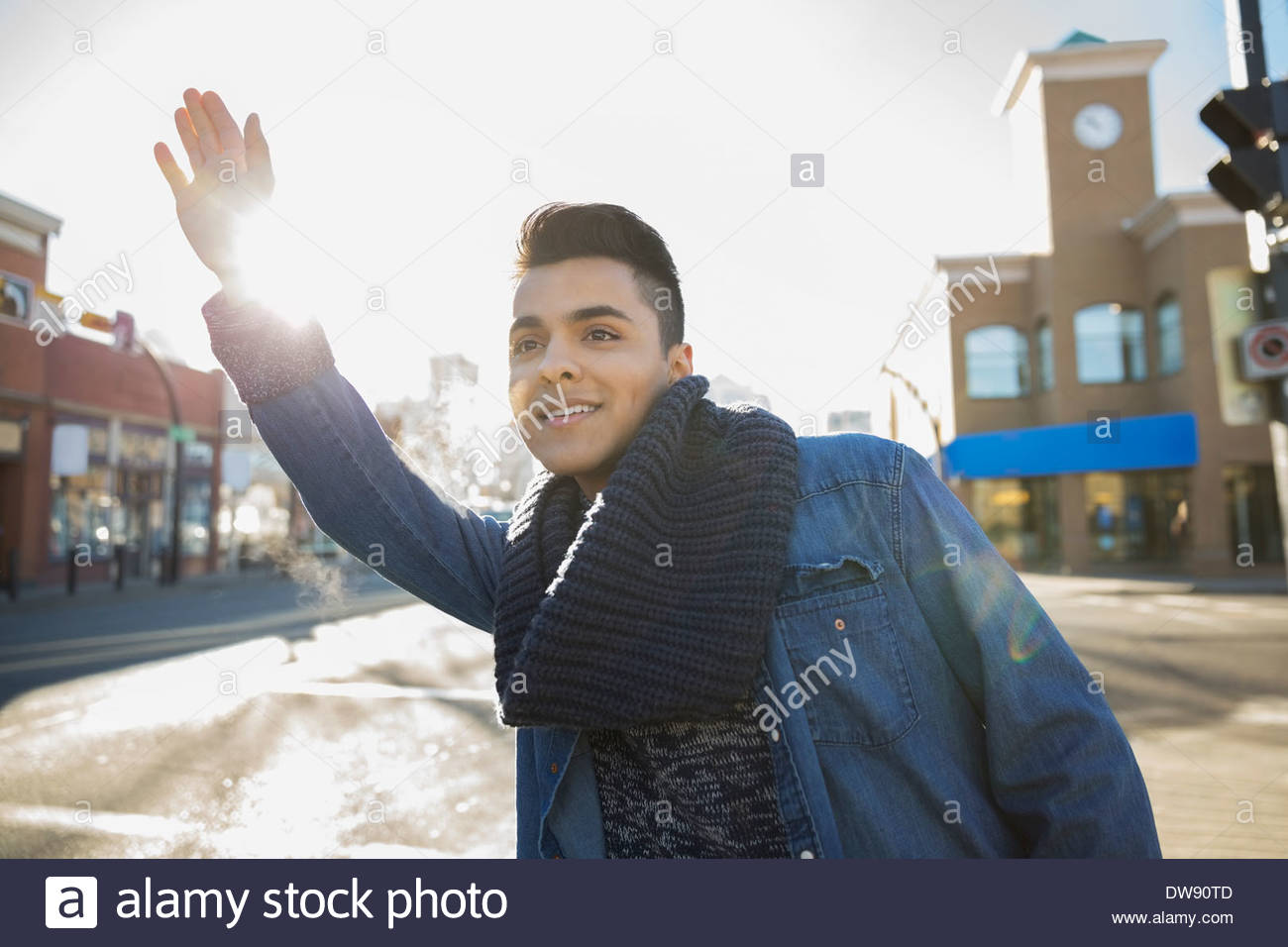 Man hailing taxi on city street - Stock Image
