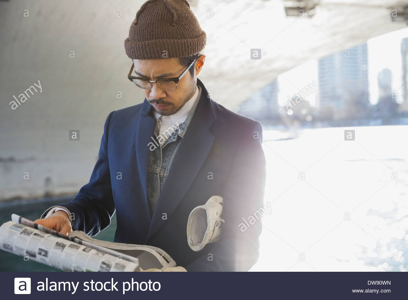 Man reading newspaper under bridge - Stock Image