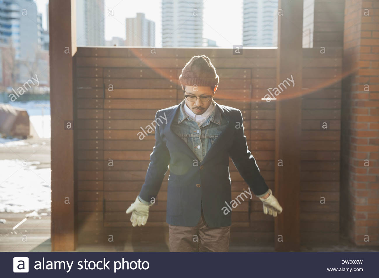 Man standing outdoors looking down - Stock Image