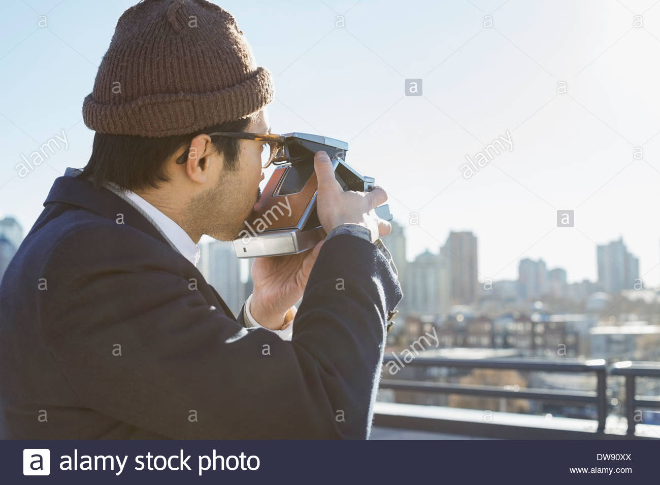 Side view of man photographing cityscape from patio - Stock Image