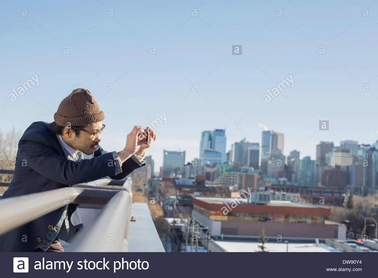 Man photographing cityscape on patio with smart phone - Stock Image