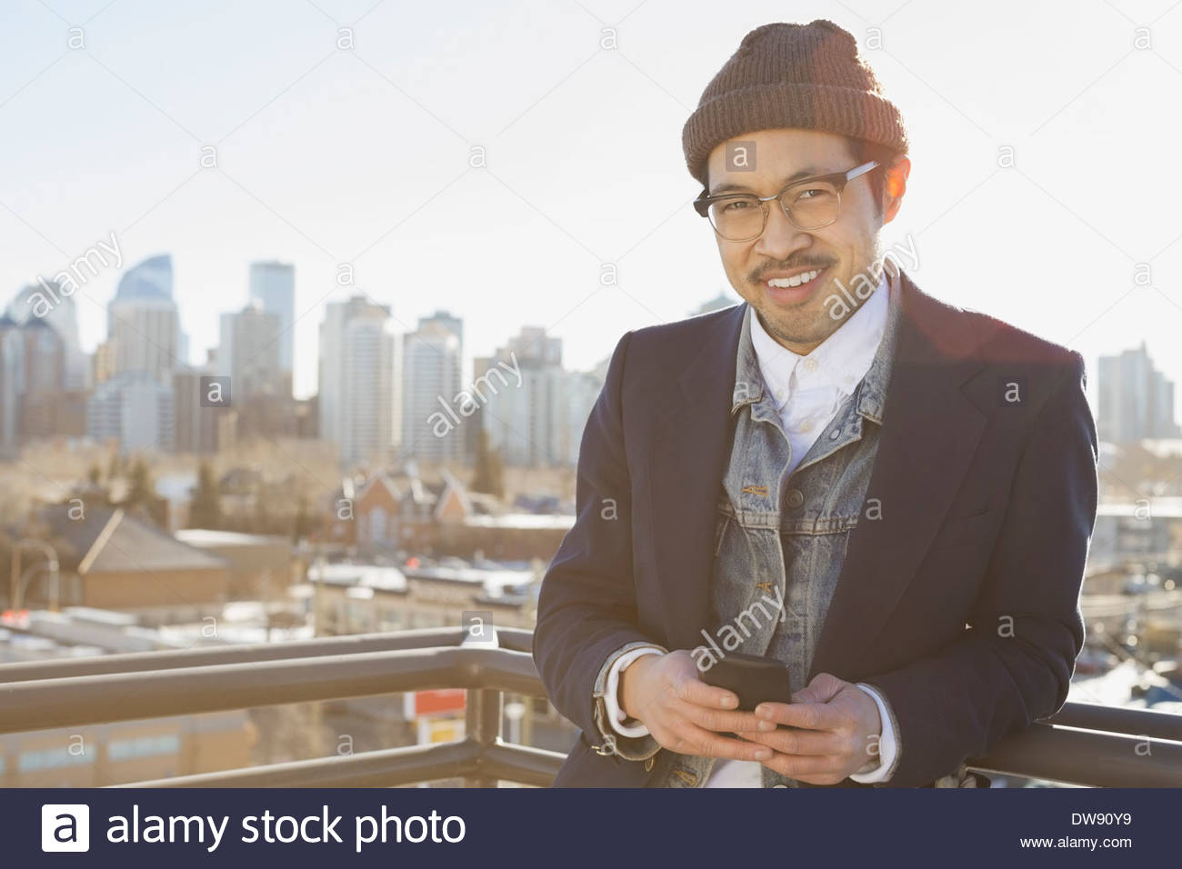 Portrait of man holding smart phone outdoors against cityscape - Stock Image