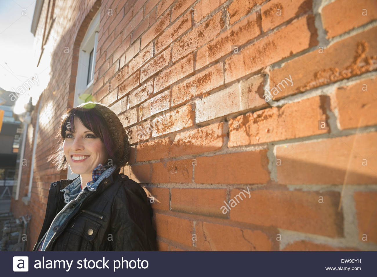 Smiling woman leaning against brick wall - Stock Image