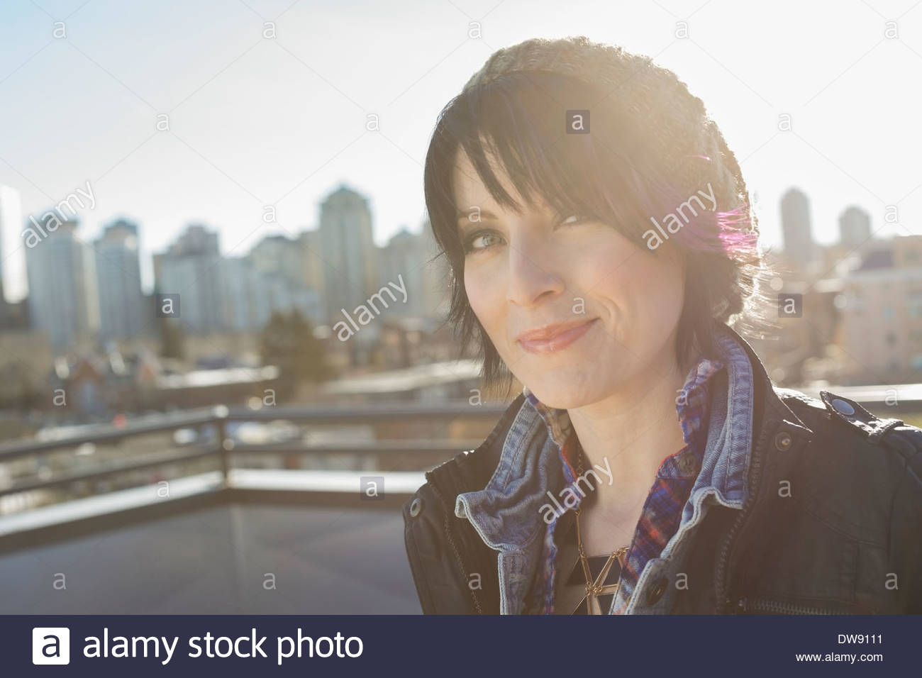 Portrait of confident woman standing outdoors - Stock Image