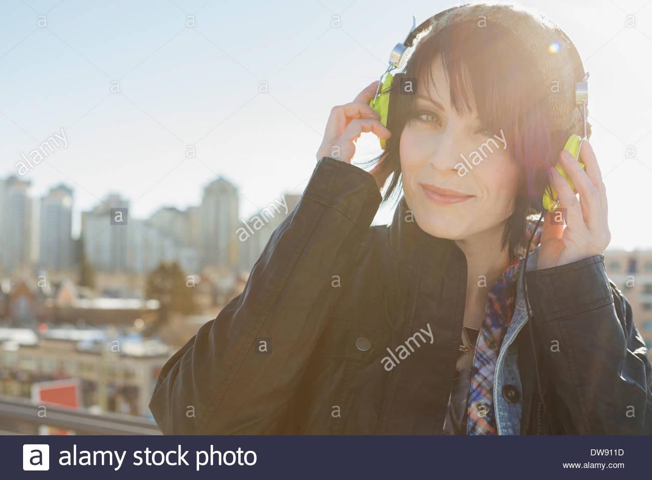 Portrait of woman listening to headphones outdoors - Stock Image