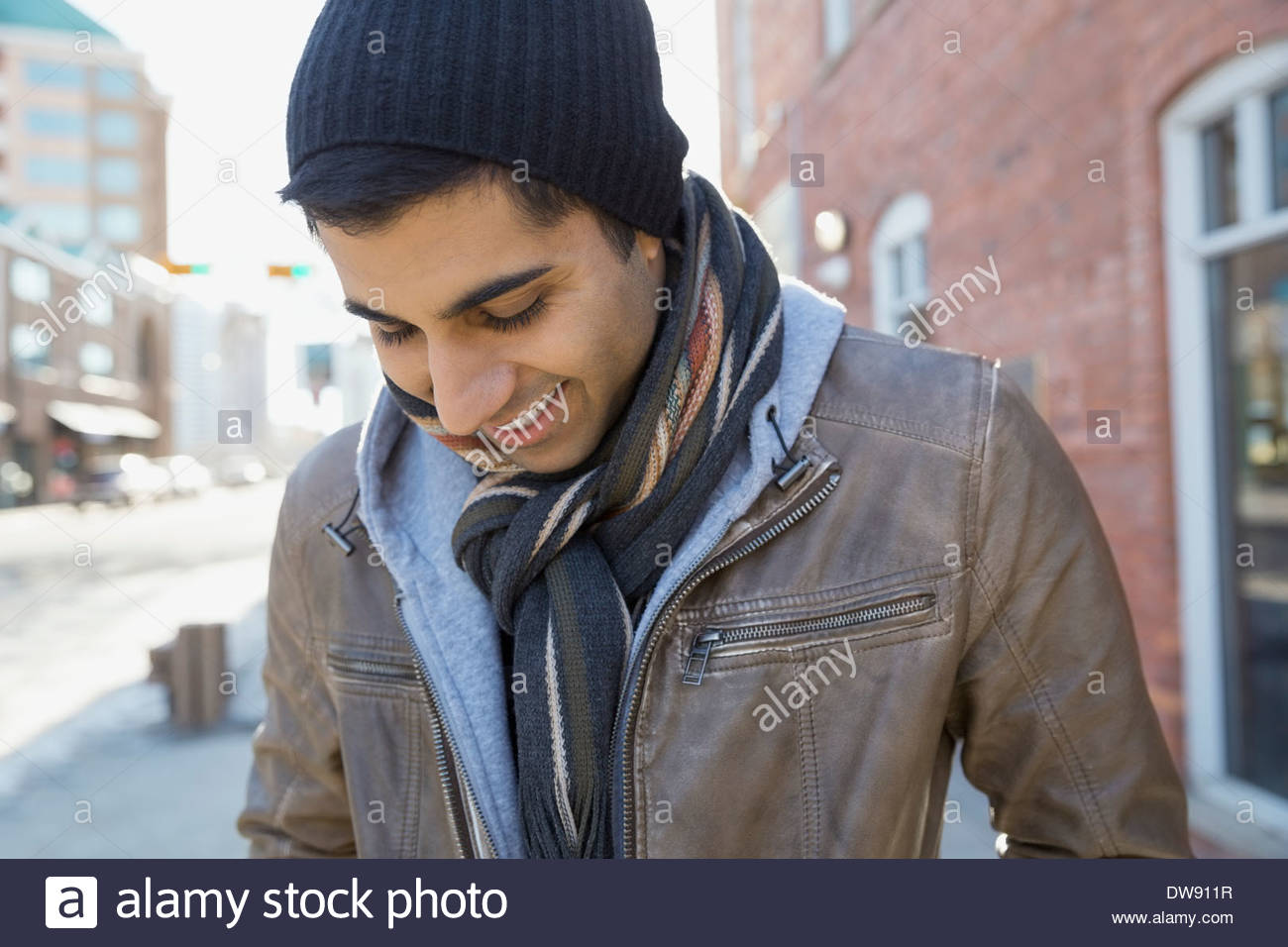 Smiling man standing outdoors looking down - Stock Image
