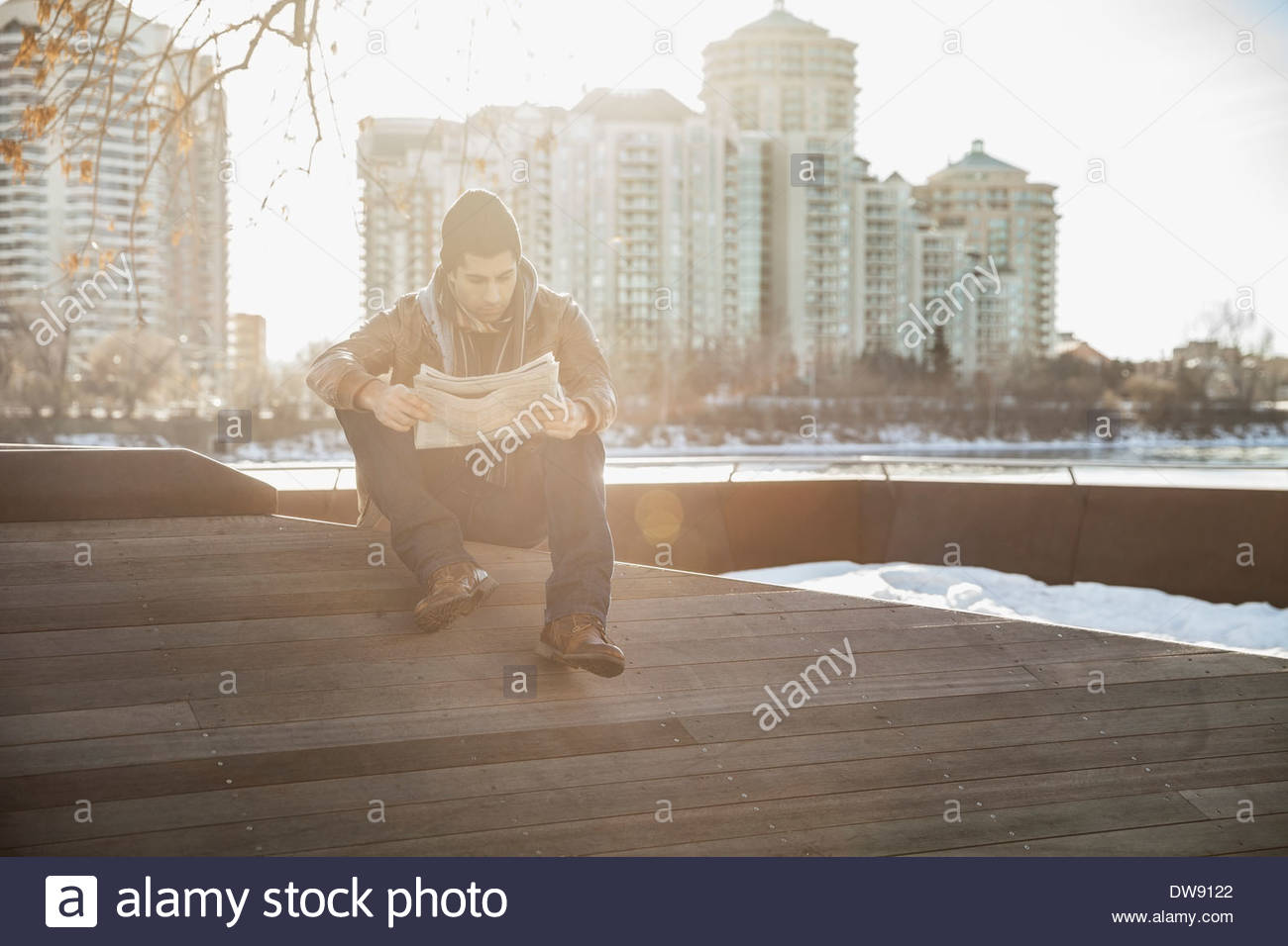 Man reading newspaper outdoors against cityscape - Stock Image