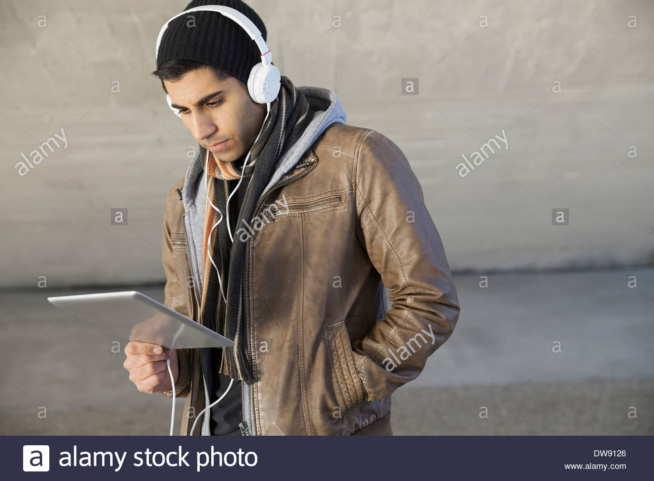Man standing outdoors with digital tablet and headphones - Stock Image