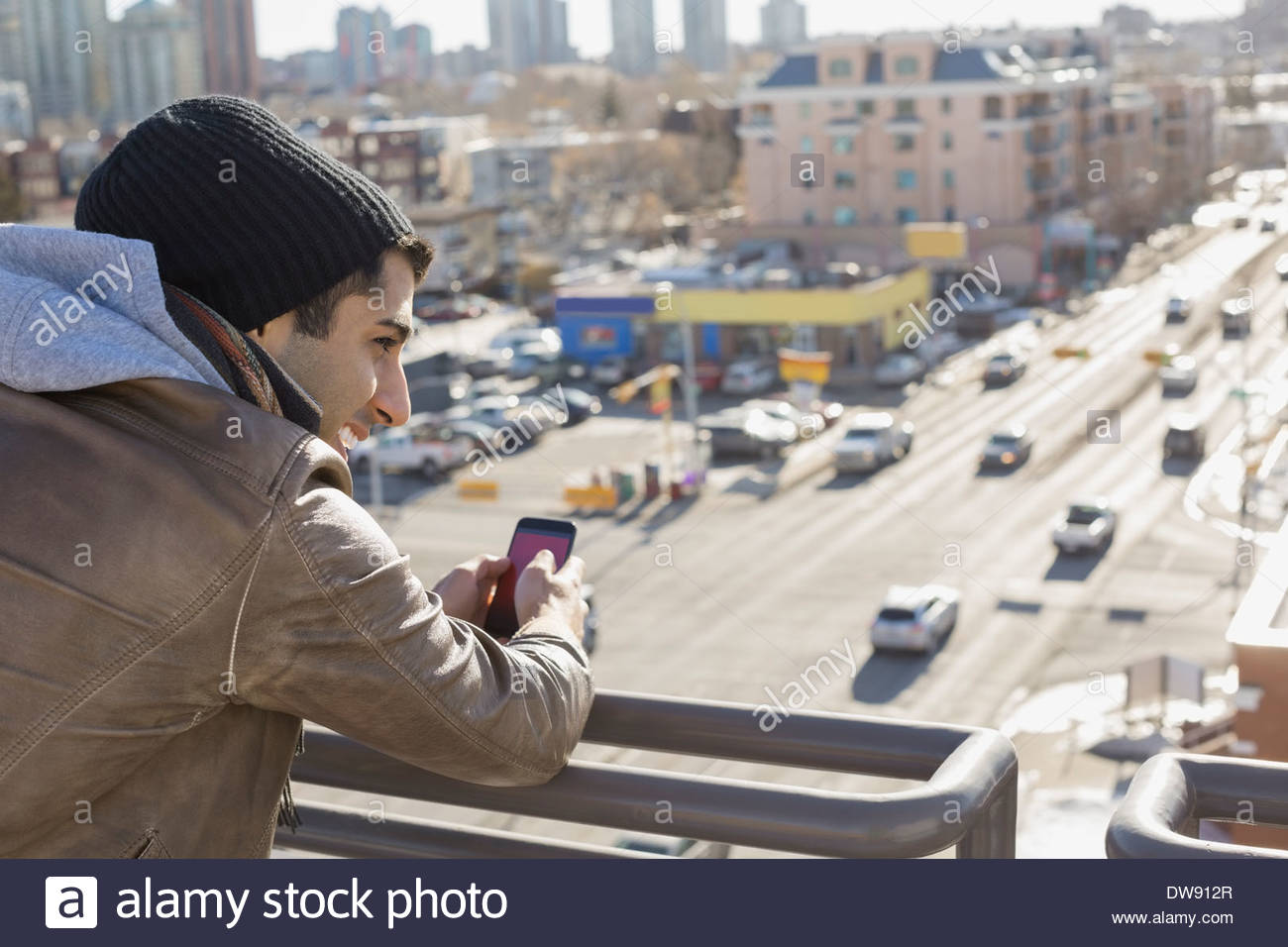 Man with smart phone leaning on patio railing Stock Photo