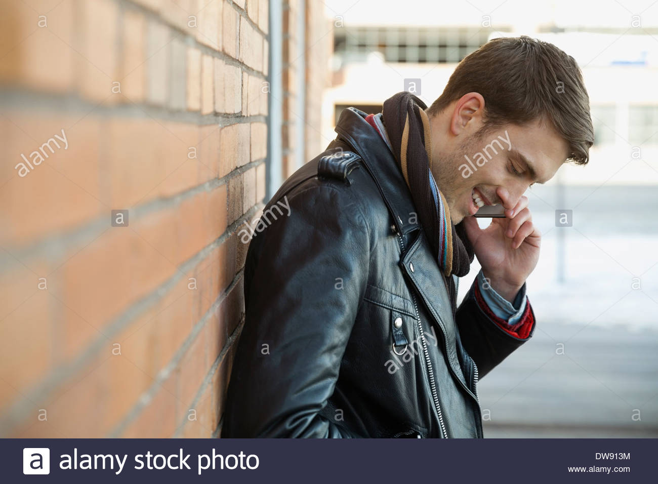Smiling man answering smart phone outdoors Stock Photo