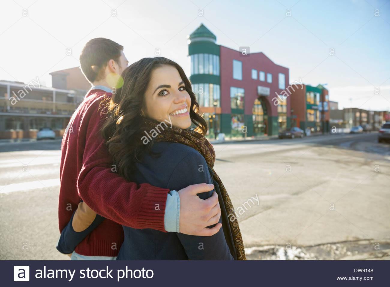 Couple walking down city street - Stock Image