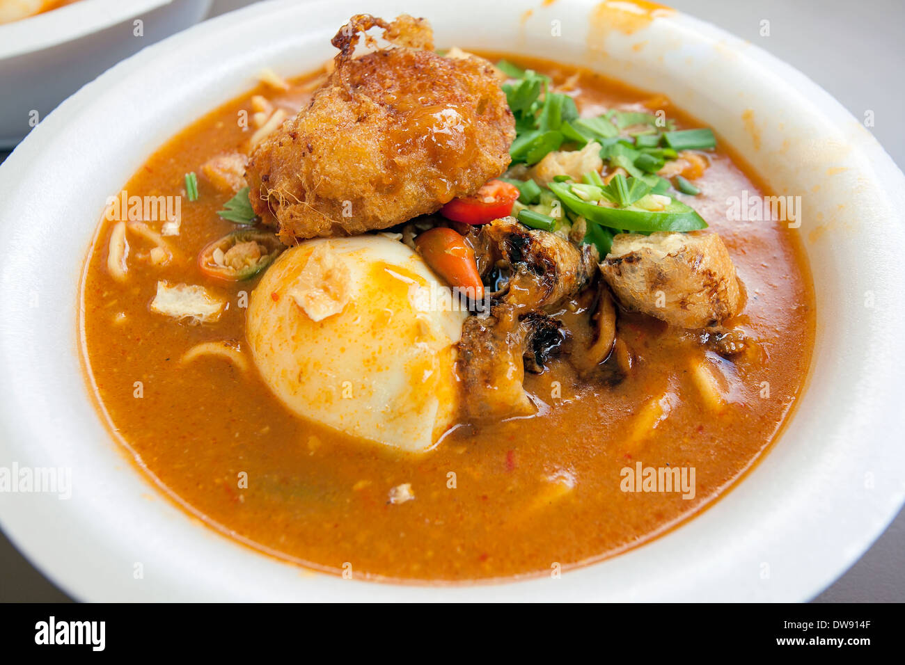 Mee Rebus Malay Local Noodle Dish with Hard Boiled Egg Fried Tofu Cut Chili Peppers and Potato Cake - Stock Image