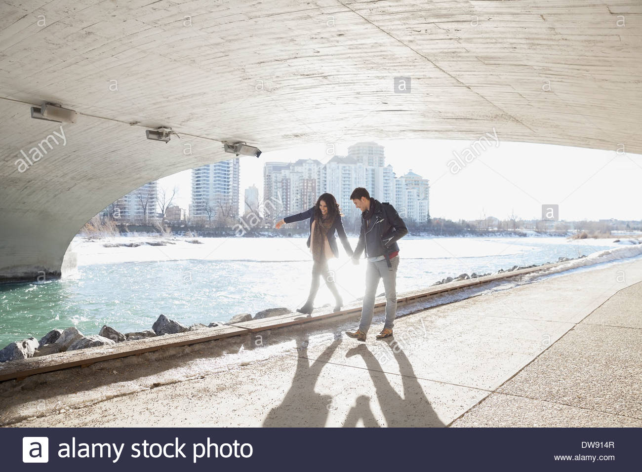 Man assisting woman walking on footpath under city bridge - Stock Image