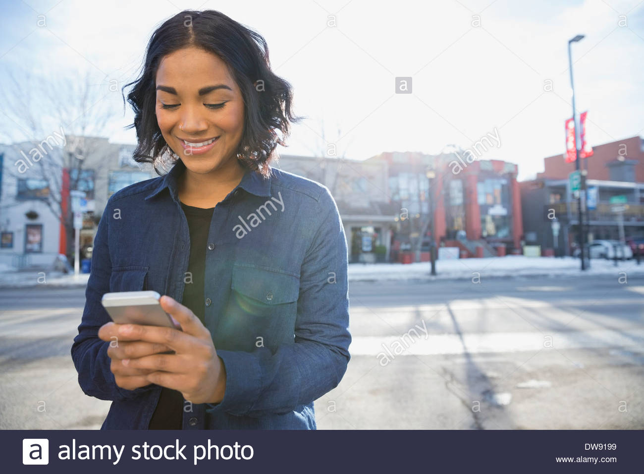 Smiling woman text messaging on city street - Stock Image
