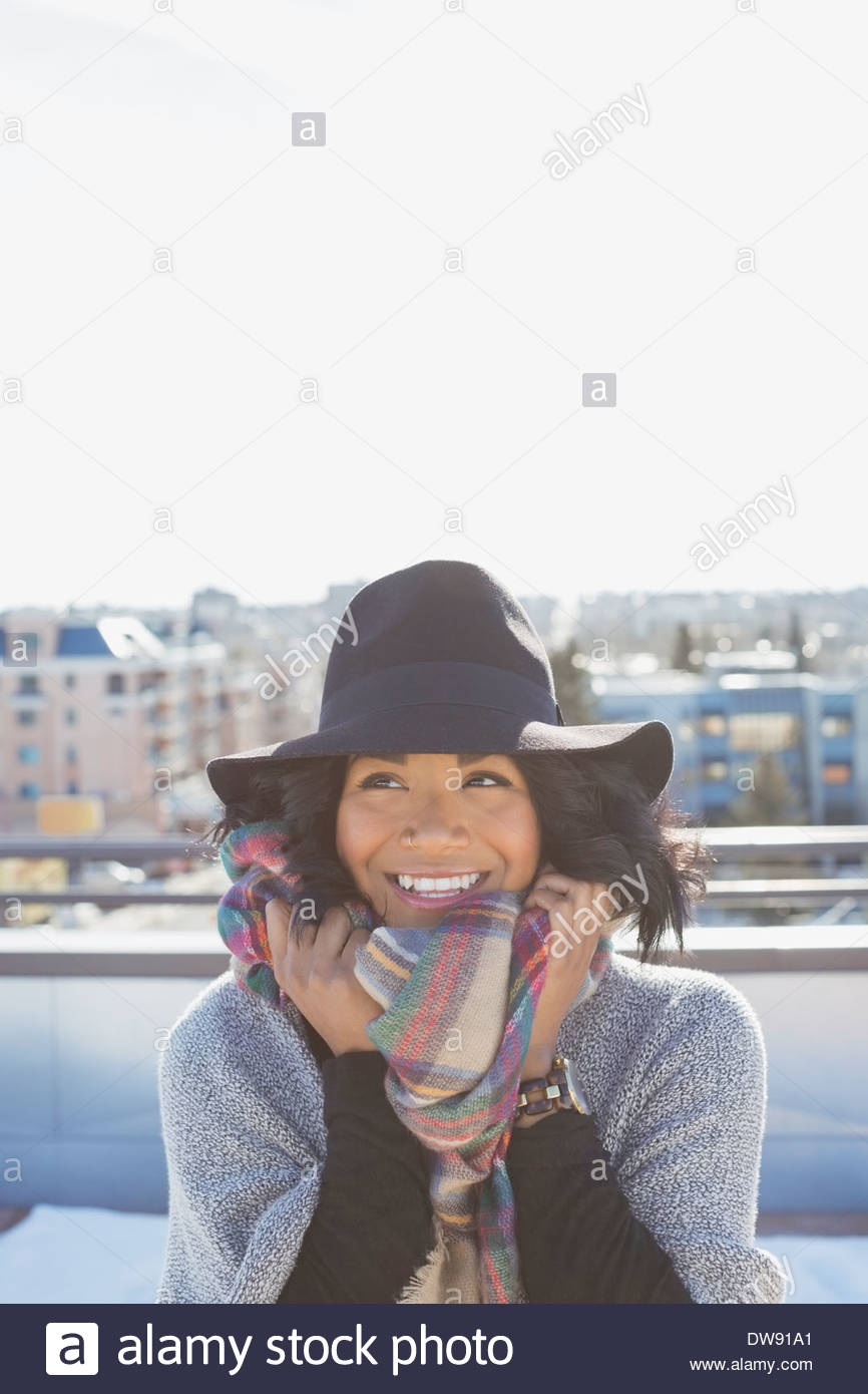Woman standing on patio with hat and poncho - Stock Image