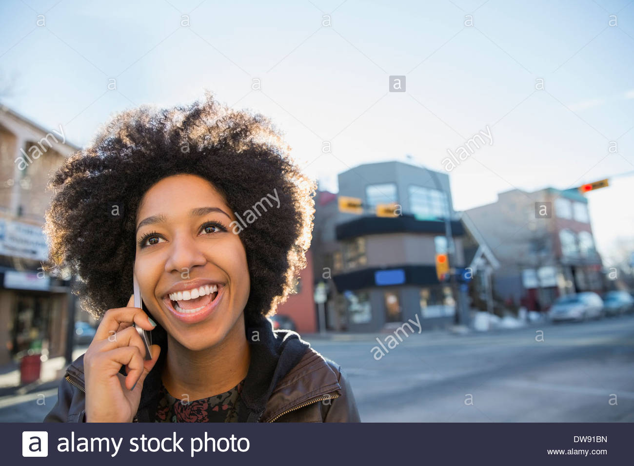 Smiling woman answering call on city street - Stock Image