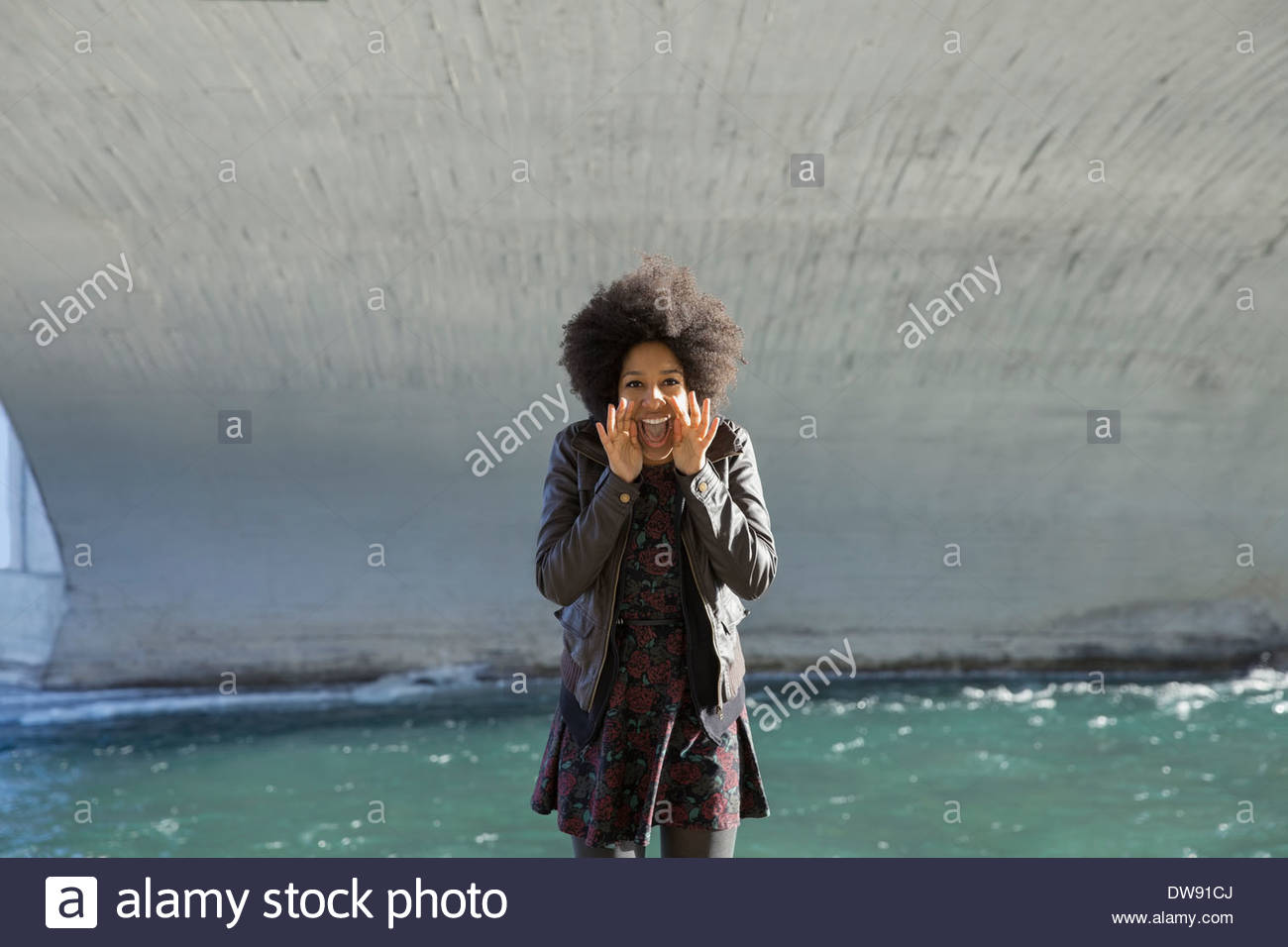 Portrait of excited woman shouting under bridge - Stock Image