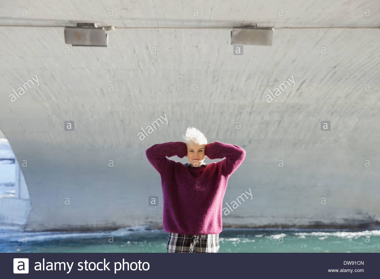 Portrait of woman with hands covering ears standing under city bridge - Stock Image
