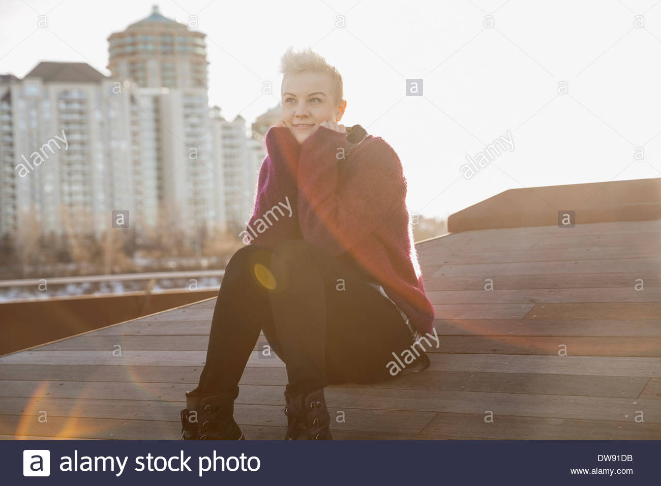 Thoughtful woman sitting outdoors - Stock Image