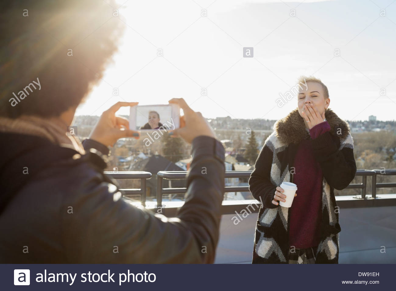 Woman being photographed by friend on patio - Stock Image