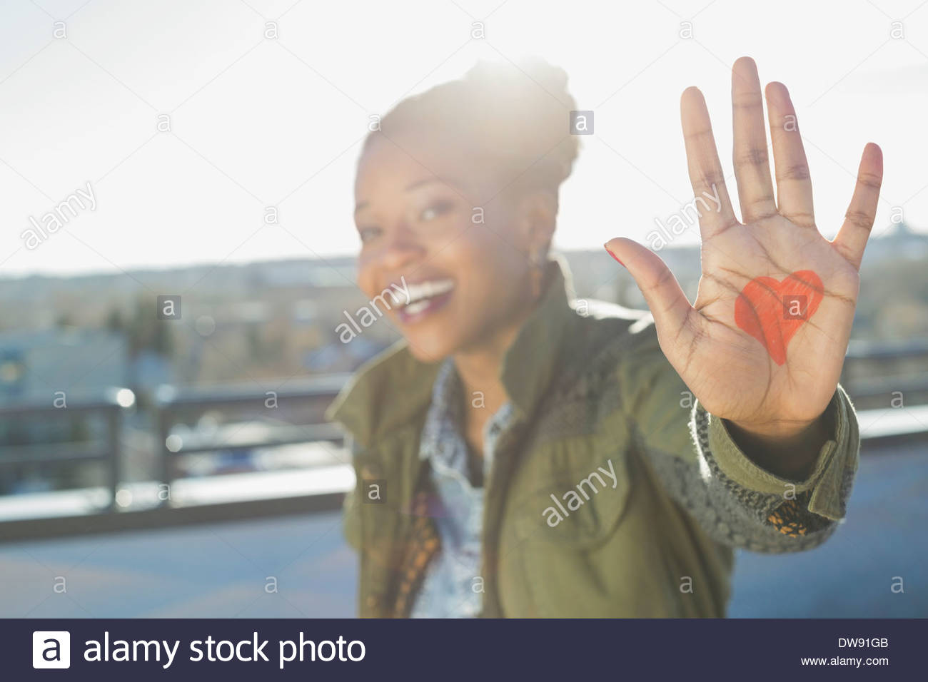 Woman showing heart shape on palm outdoors - Stock Image