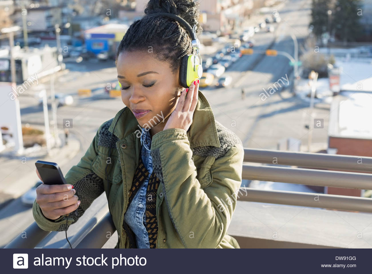 Relaxed woman listening to music on patio - Stock Image