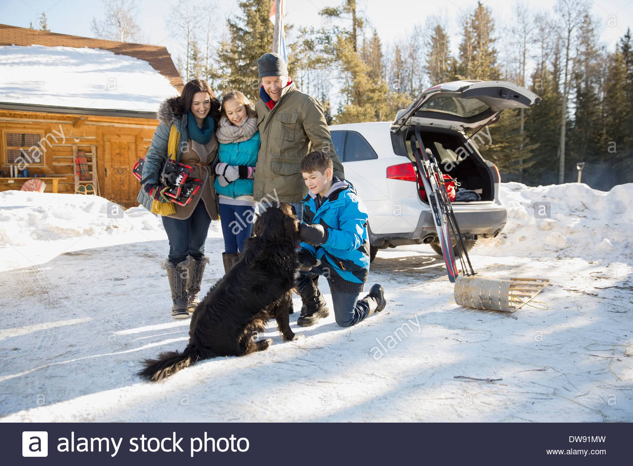 Family gathered outside log cabin in winter - Stock Image
