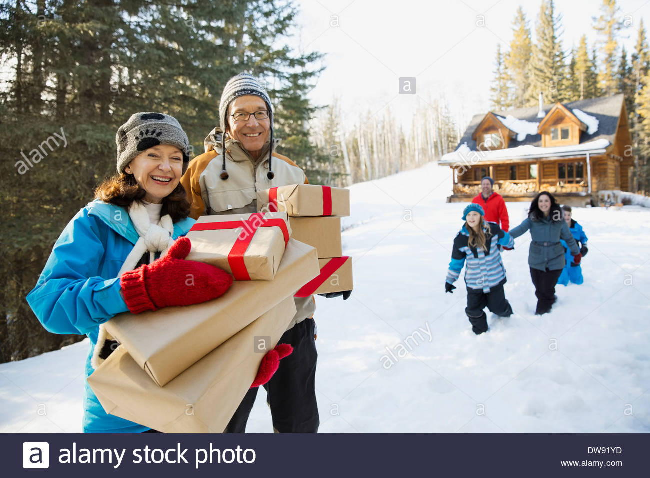 Portrait of senior couple holding Christmas presents outdoors Stock Photo