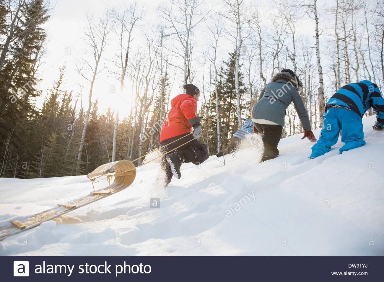 Family walking up hill pulling toboggan - Stock Image