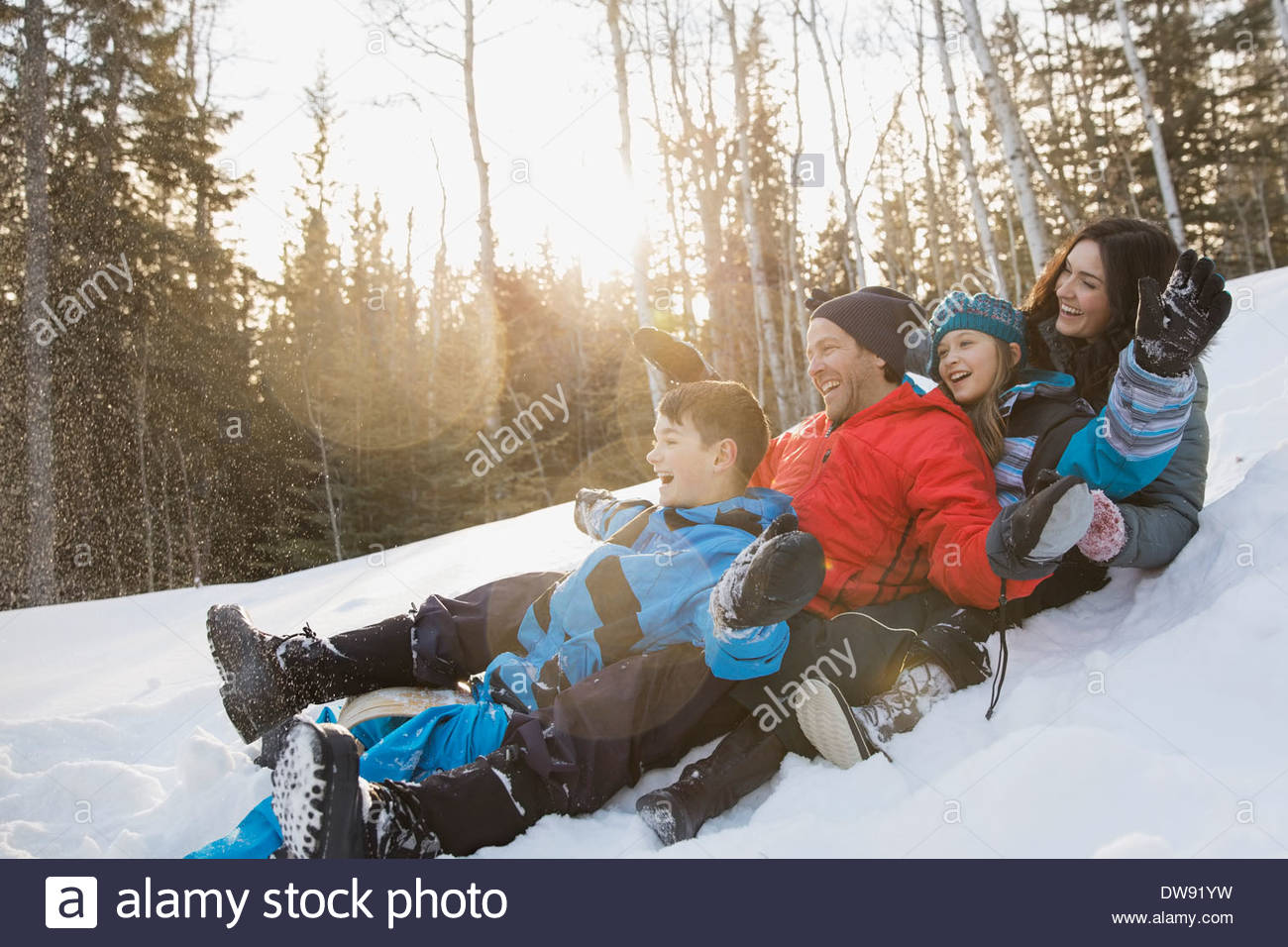 Family riding on toboggan down hill - Stock Image