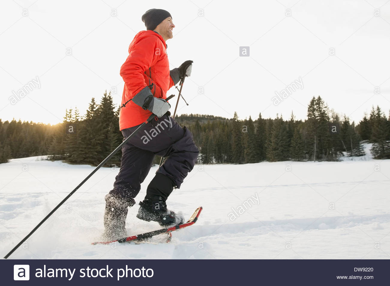 Side view of man snowshoeing - Stock Image