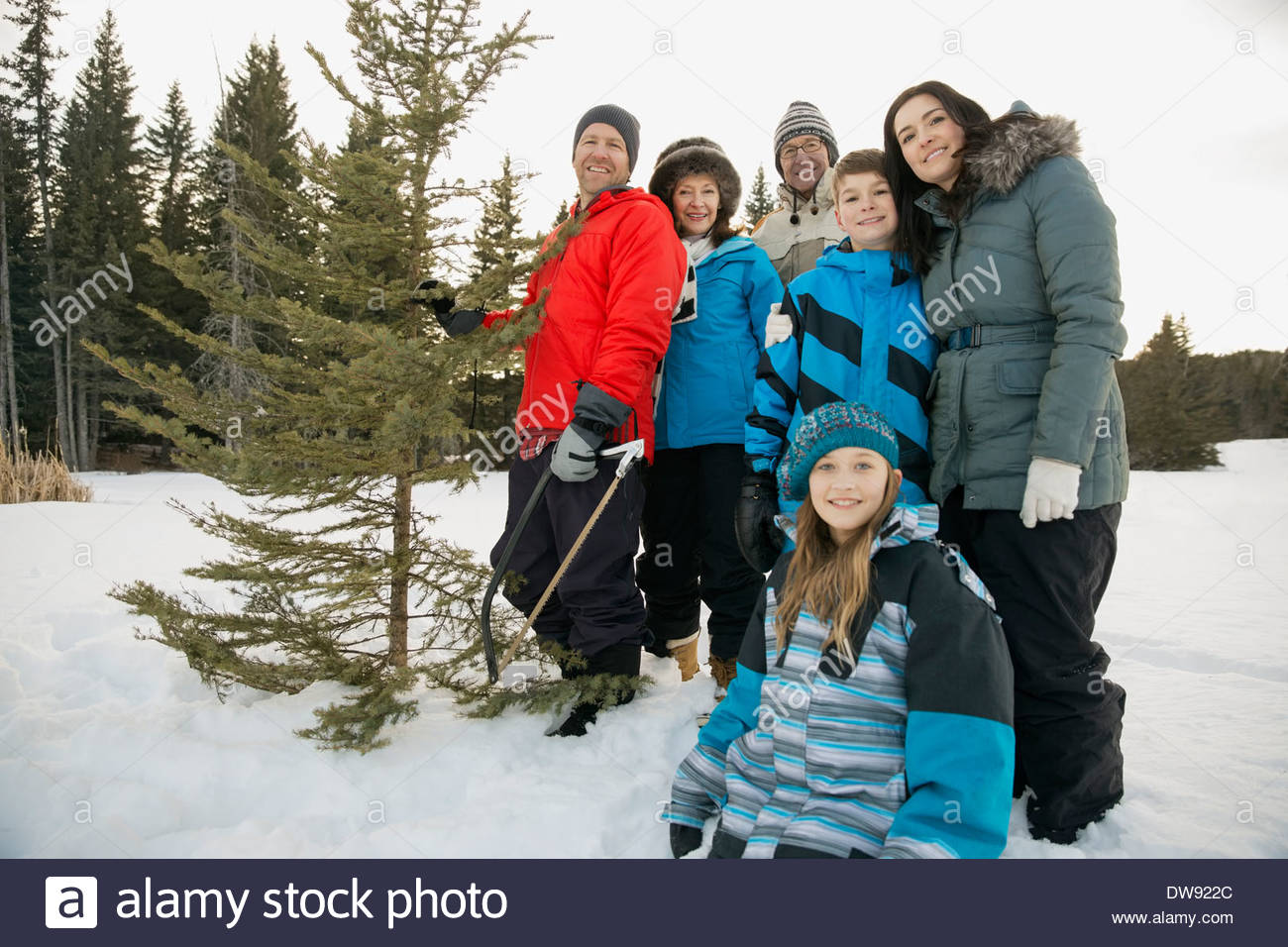 Portrait of family with Christmas tree in snow Stock Photo