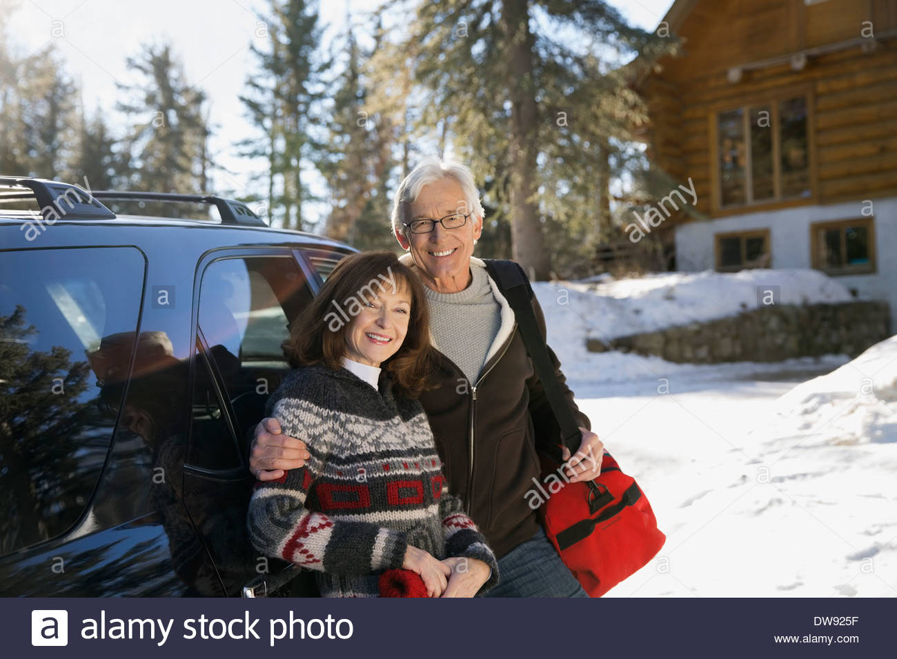 Portrait of senior couple standing by vehicle - Stock Image