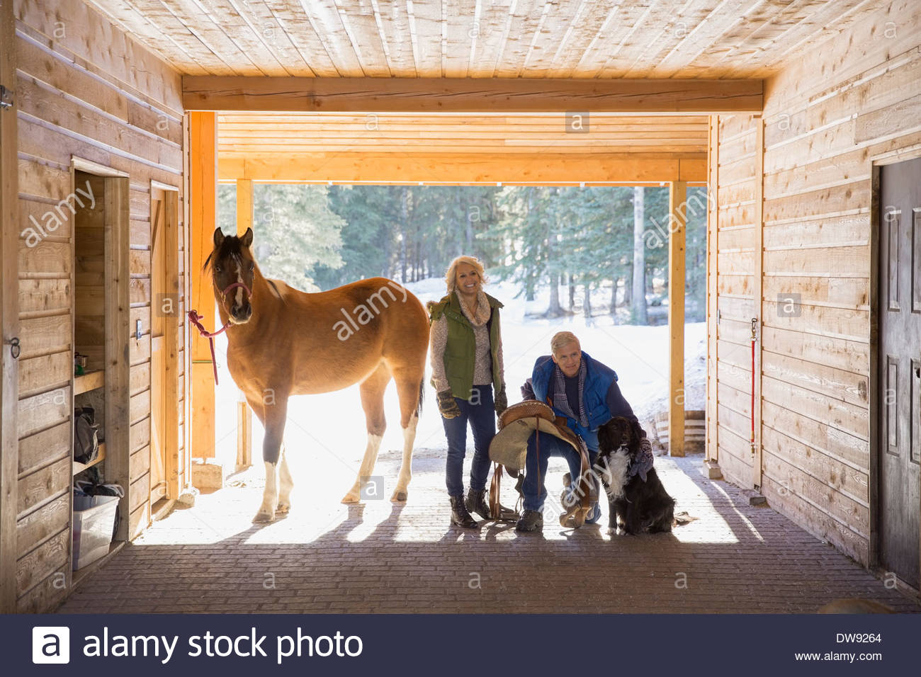 Smiling couple with horse and dog in stable - Stock Image