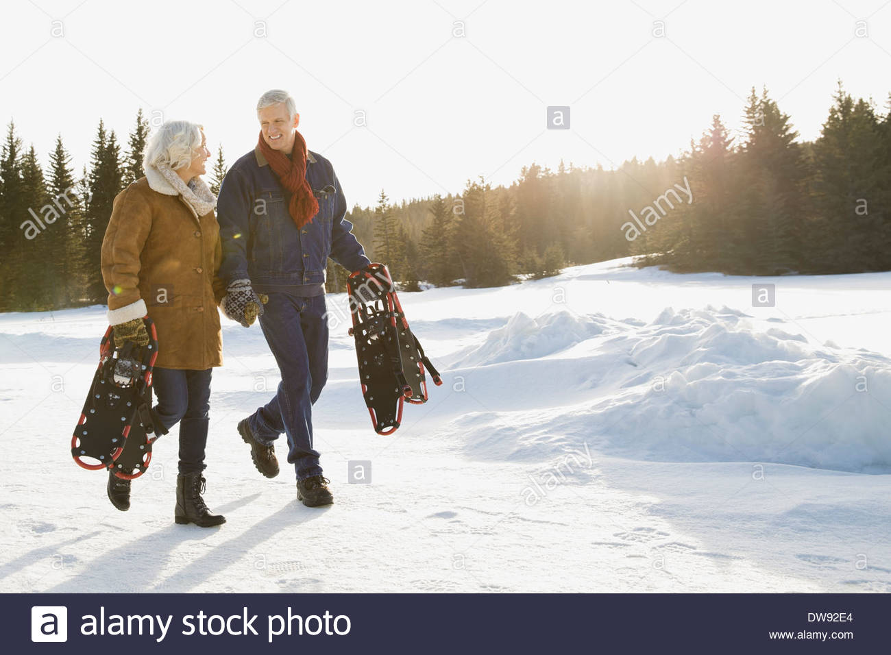 Couple carrying snowshoes outdoors - Stock Image
