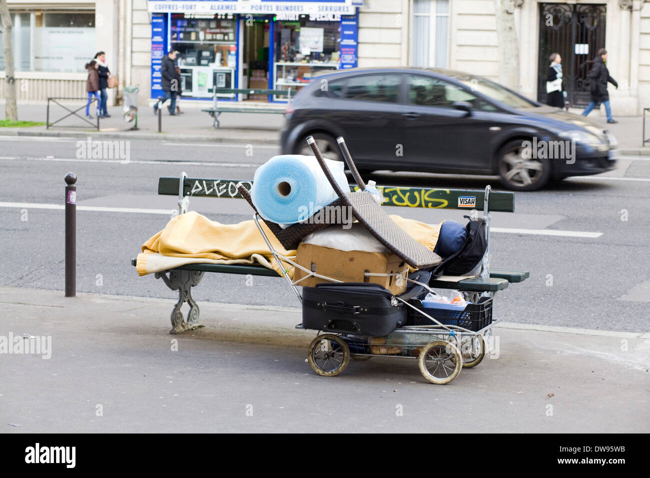 A Person sleeping rough on a street bench in Paris France - Stock Image