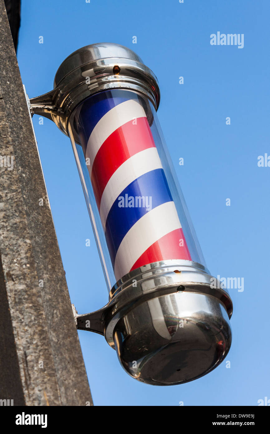 Traditional red and white barber's pole outside a hairdresser's shop. - Stock Image