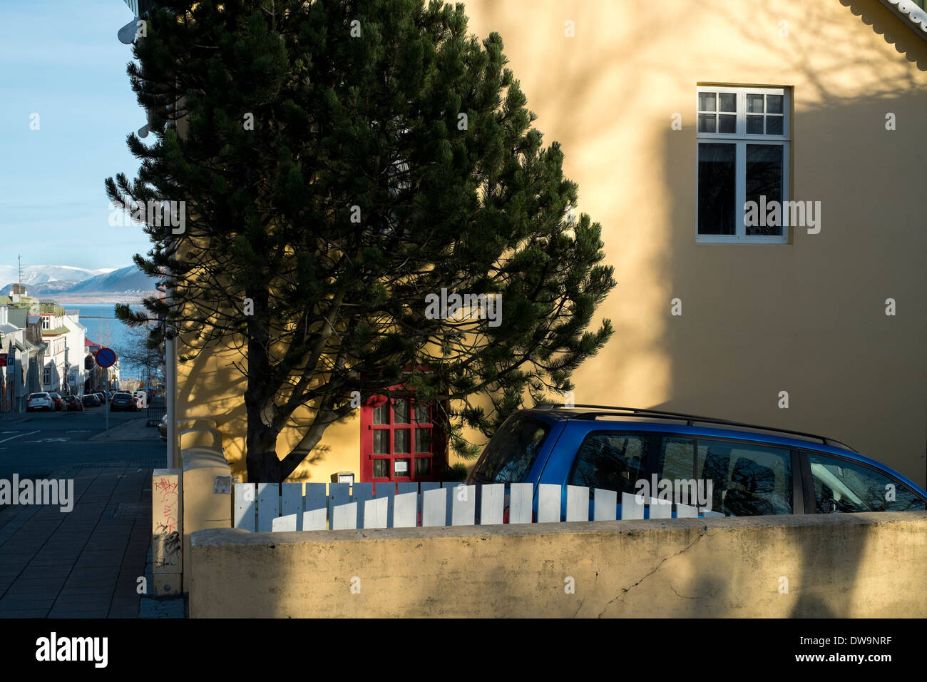 Car parked behind garden fence with tree. Revkjavik, Iceland - Stock Image