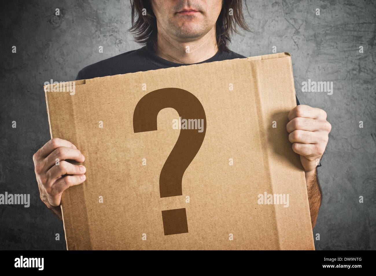 Man holding cardboard poster with question mark printed on. - Stock Image