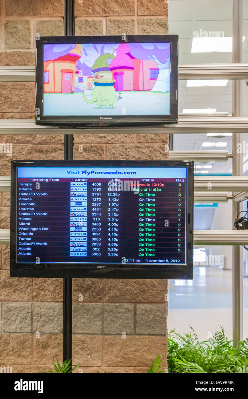 Animated cartoon plays on screen a above arrival information at Pensacola International Airport in Pensacola, Florida - Stock Image