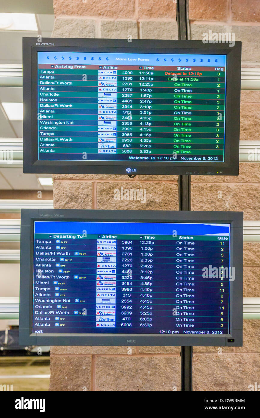 Information screens show arrivals and departures at Pensacola International Airport in Pensacola, Florida - Stock Image