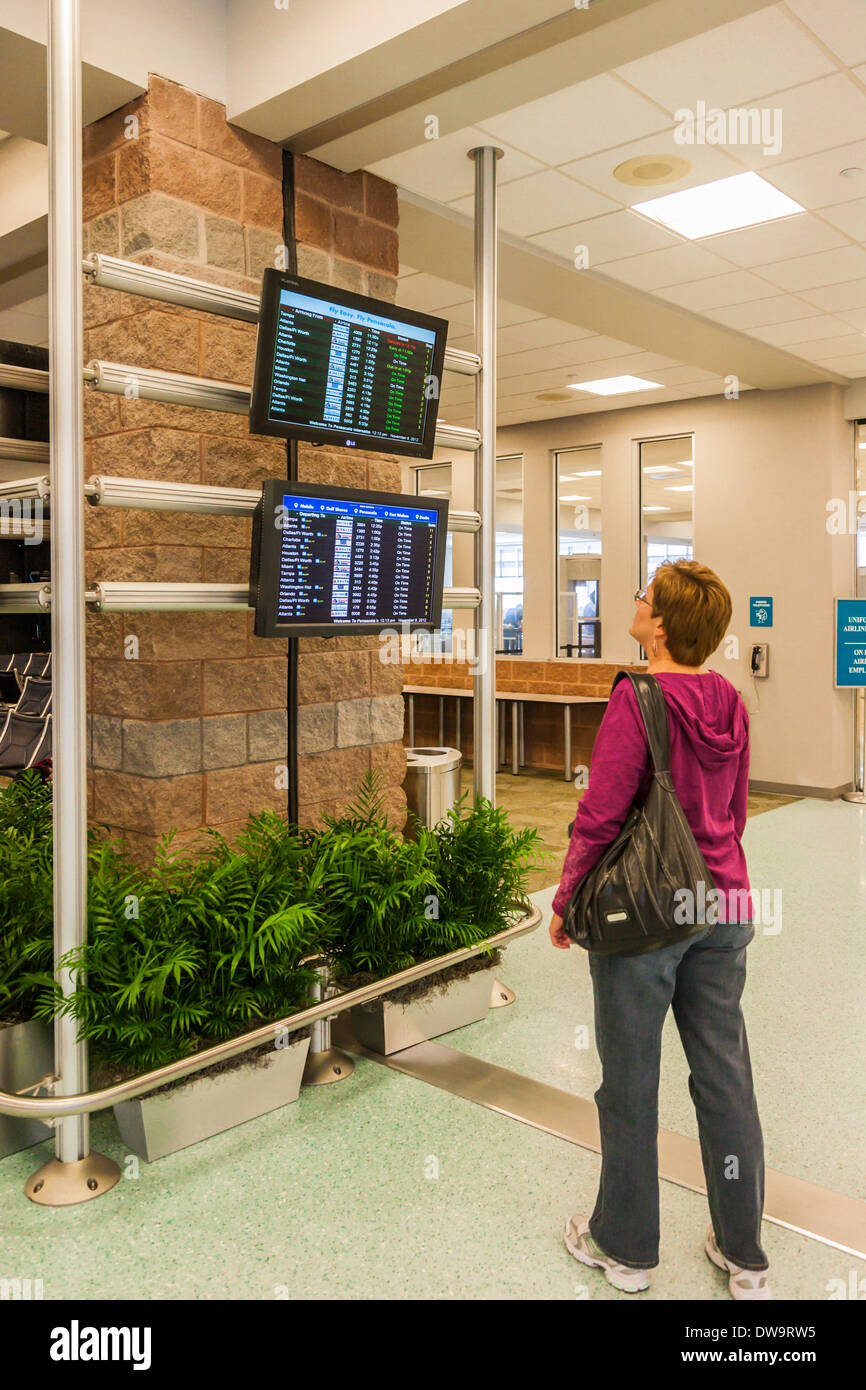 Woman looking a arrival and departure screens at Pensacola International Airport in Pensacola, Florida - Stock Image