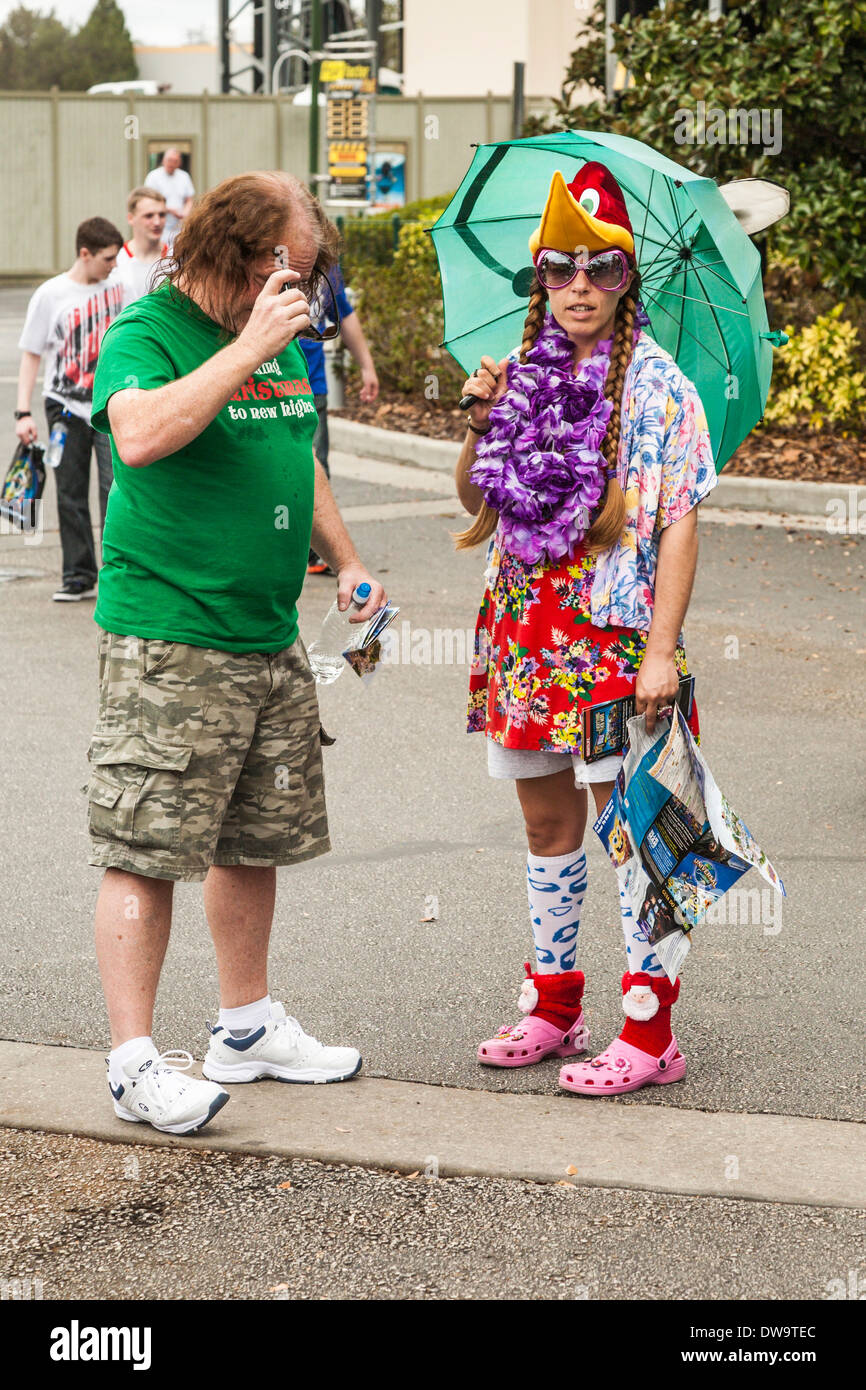 Park guest takes a close look at a wildly dressed employee in Universal Studios theme park in Orlando, Florida - Stock Image