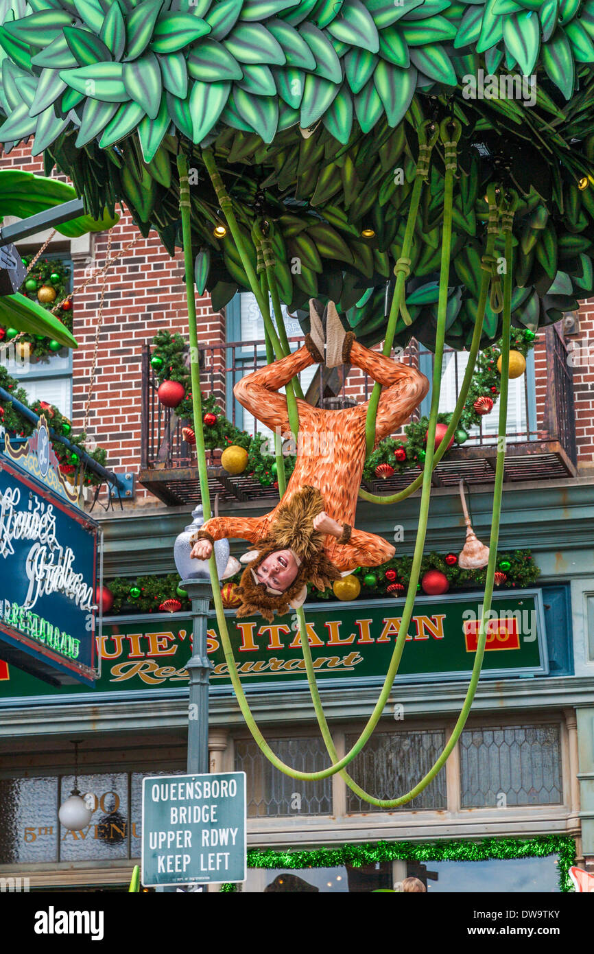 Young male acrobat in monkey costume hanging upside down on parade float in Universal Studios theme park in Orlando, Florida - Stock Image