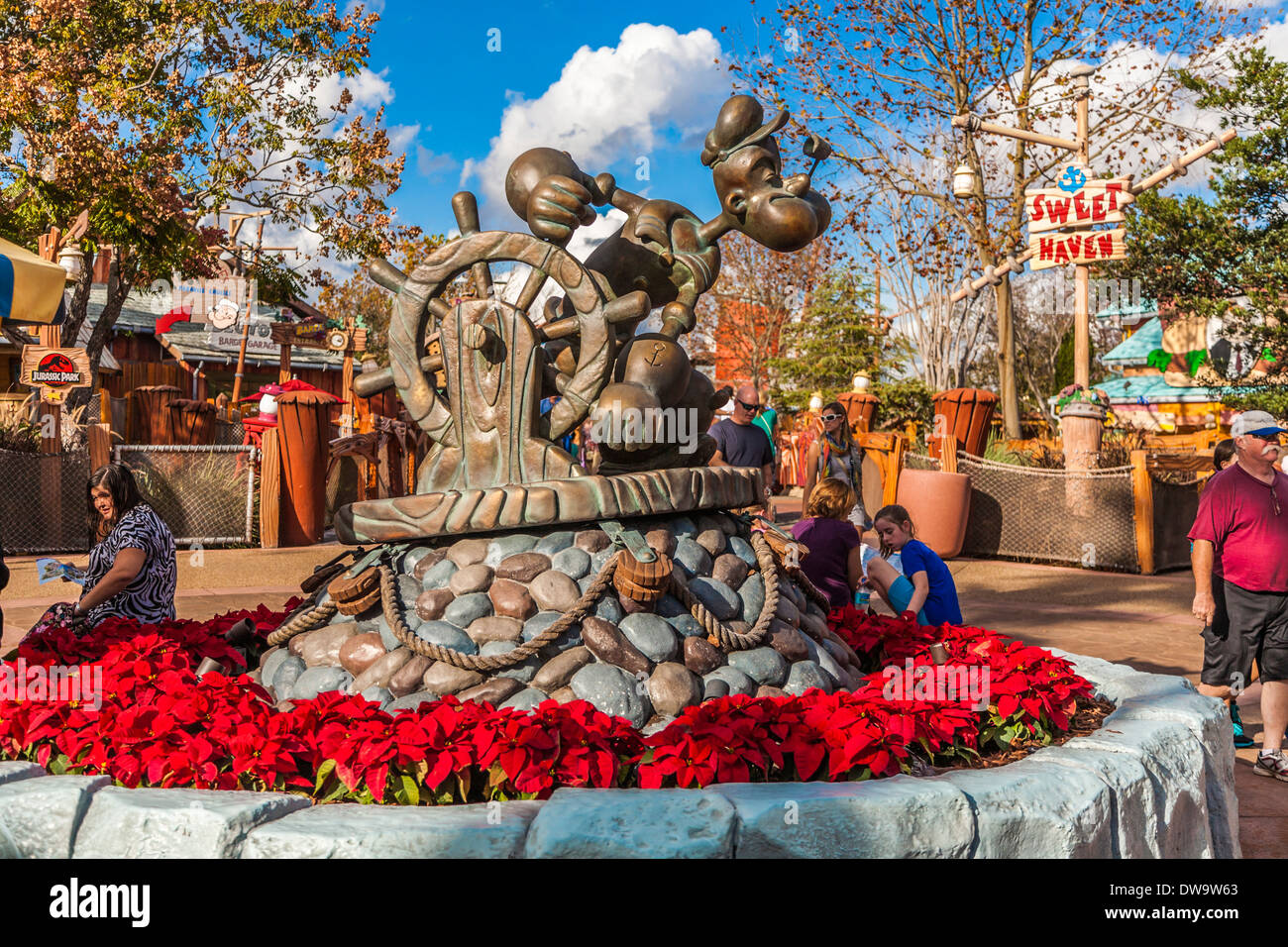 Park guests rest at base of Popeye statue in Toon Lagoon at Universal Studios Islands of Adventure in Orlando, Florida - Stock Image