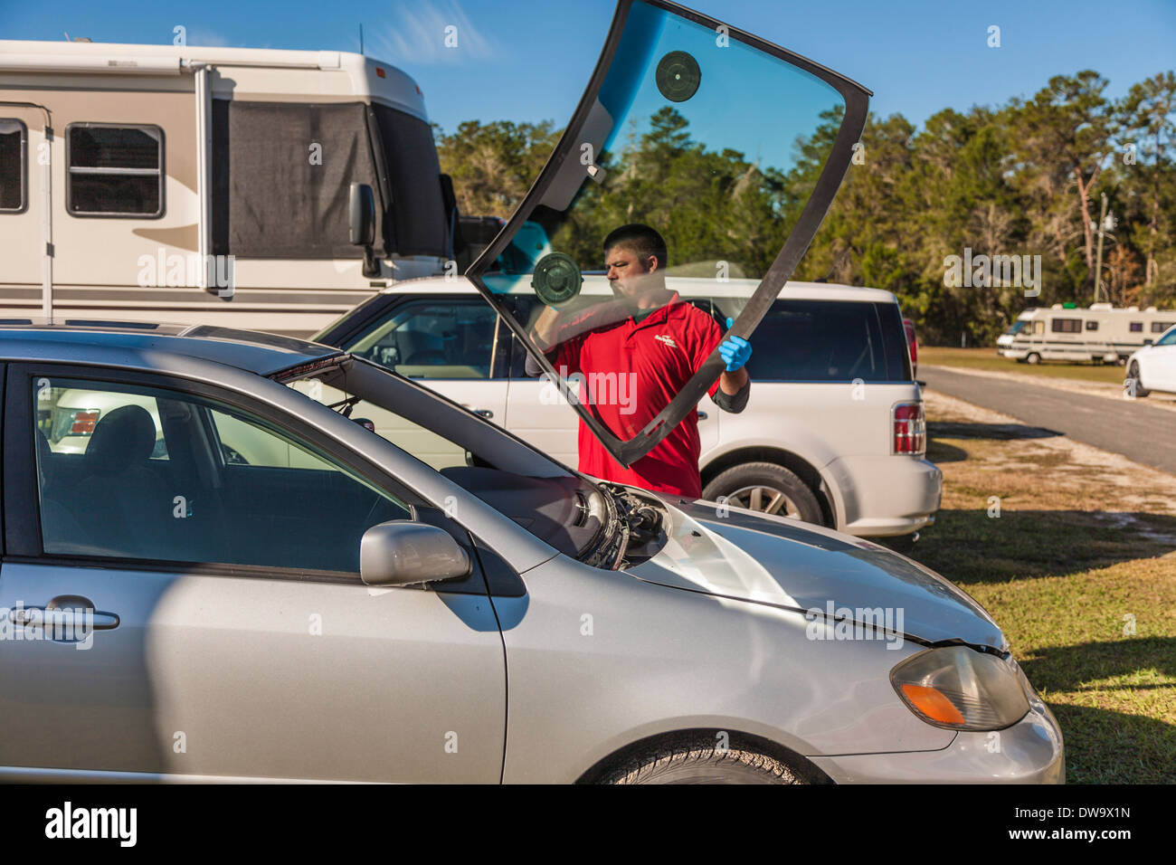 Mobile service technician replacing windshield glass on Toyota Corolla - Stock Image